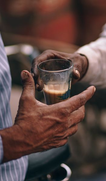 A chai seller  handing a cup of chai to a customer in New Delhi