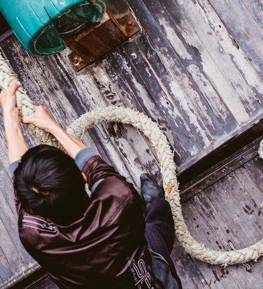 A junk ship crew member hauls rope to raise the sails