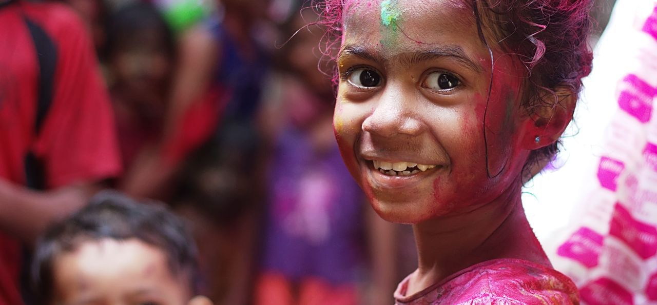Young girl covered in colourful powder for Holi