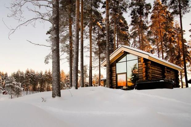 Snowy cabin in the woods at Arctic Retreat in Sweden