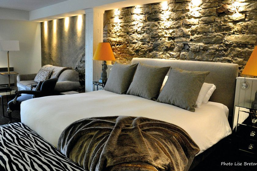 Guest room with stone detailing at Auberge St Antoine