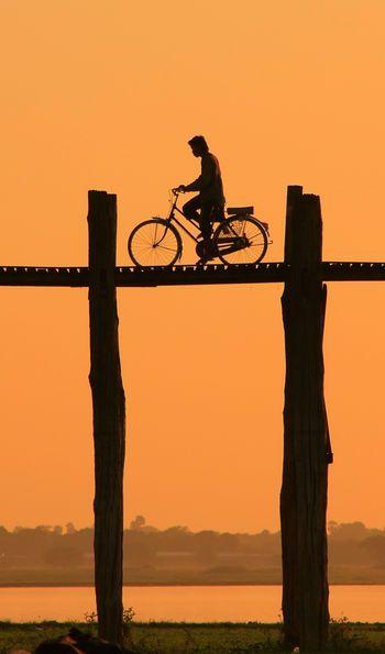Cycling over U Bein Bridge at sunset in Amarapura, Mandalary Region, Burma