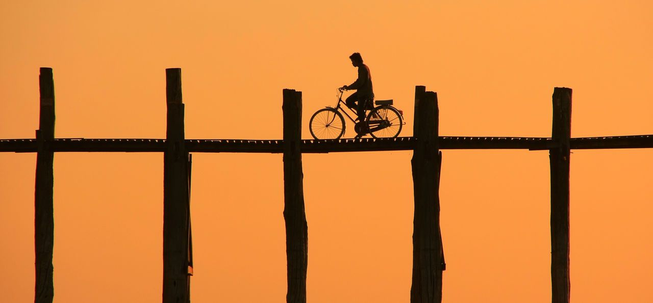 Cycling over U Bein Bridge at sunset in Amarapura in Mandalay region, Burma (Myanmar)