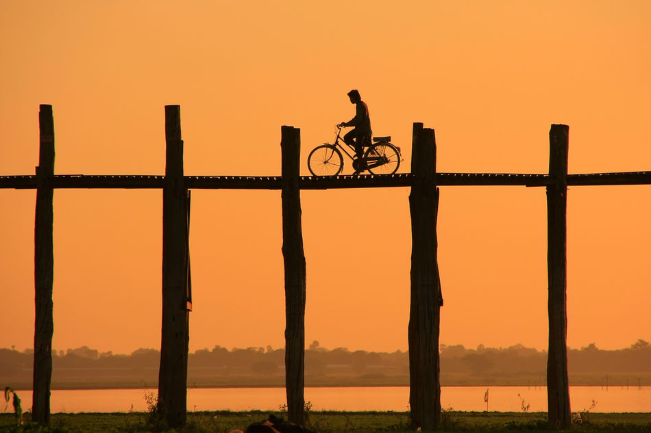 man cycling over U Bein Bridge at sunset in Amarapura in the Mandalay region of Myanmar