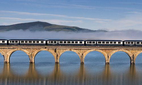El Transcantábrico Gran Lujo train on an arched bridge over Spanish river