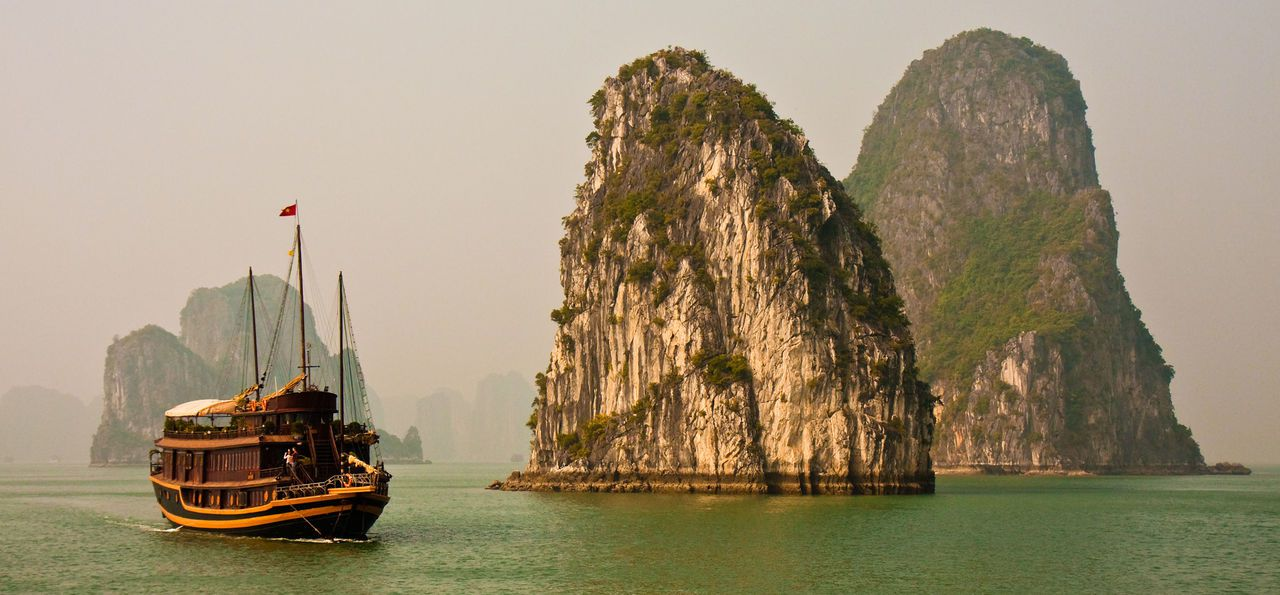 A ship sails past a limestone pillar in Halong Bay