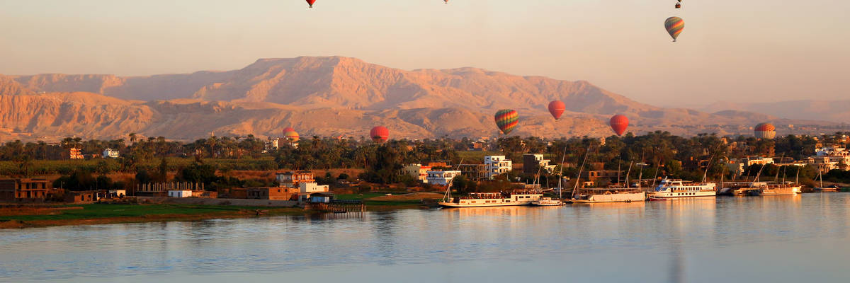 Many Hot air balloons floating over the Nile River in Luxor at sunrise
