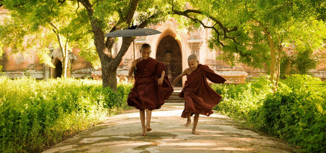 Monks running in happiness outside a temple in Myanmar (Burma)