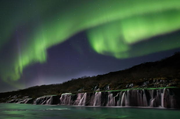 Northern Lights by a waterfall in Husafell in West Iceland