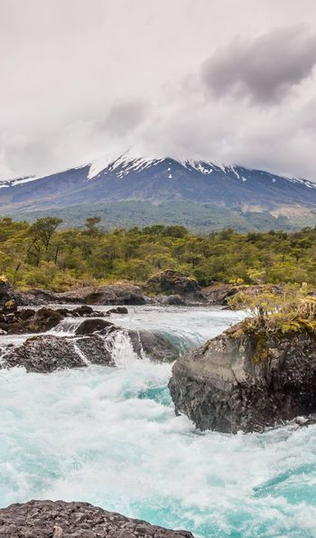 Petrohue Falls and Osorno Volcano with its snow peak in Puerto Varas in cloudy weather, south of Chile