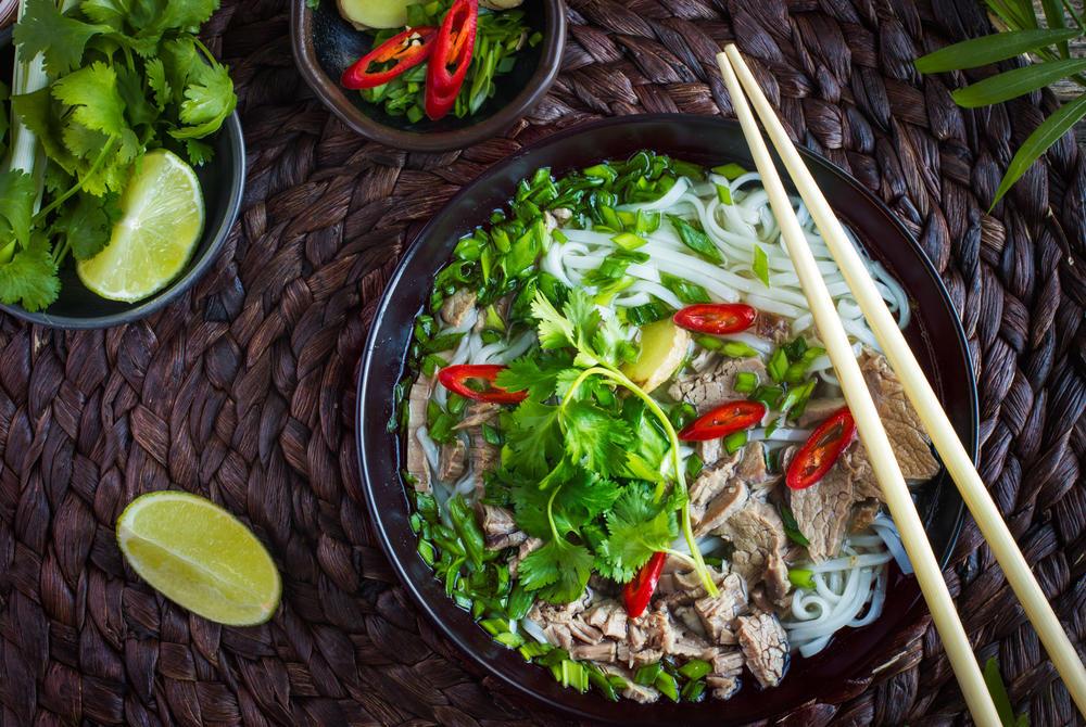 A bowl of Vietnamese pho with chopsticks