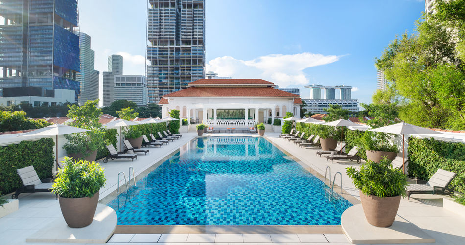 The rooftop pool of Raffles Hotel, surrounded by deckchairs and modern buildings