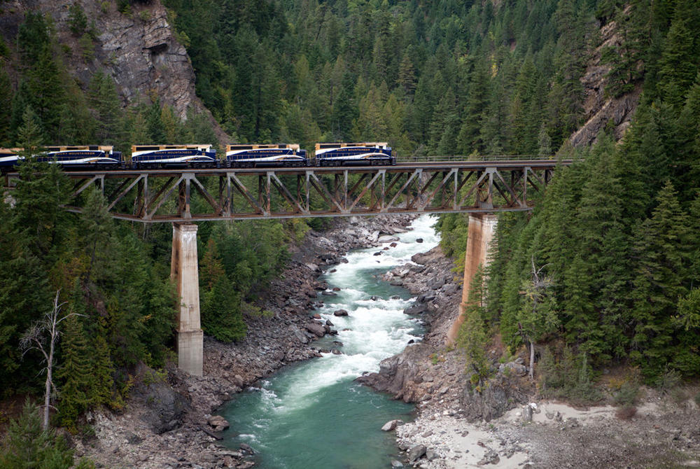 Rocky Mountaineer luxury train rail journey passing over a river
