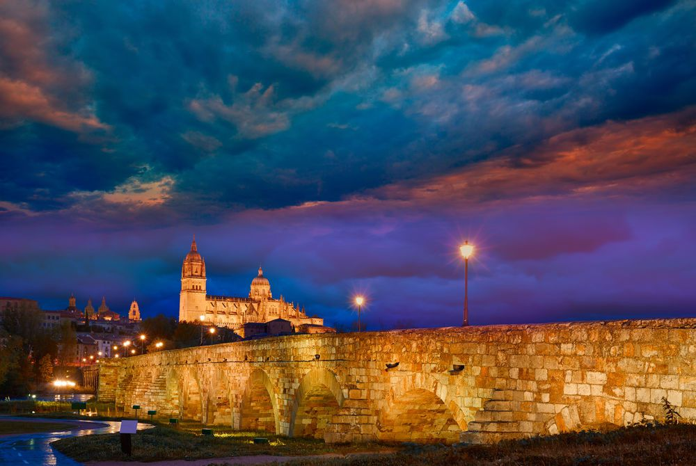 Salamanca skyline at sunset and Roman bridge over Tormes River in Spain