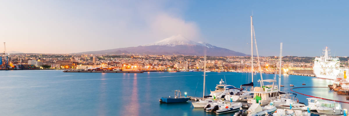 Skyline of Catania and its harbor with snowy volcano Etna