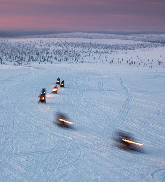 Snowmobiles in motion. Lapland, Finland