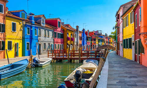 Street with colorful buildings and canal in Burano island, Venice, Italy