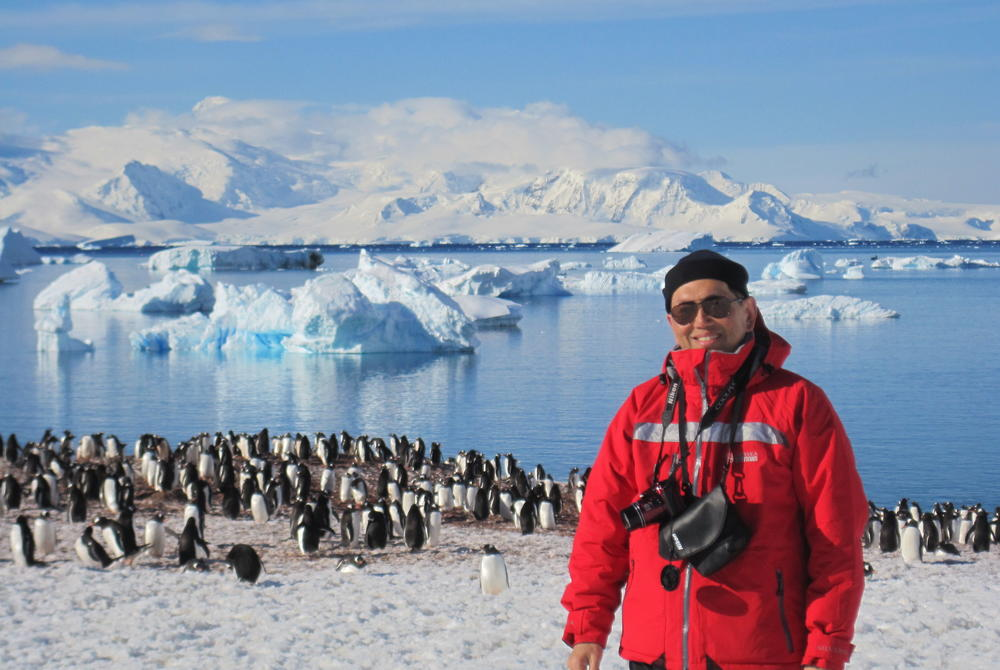 Wexas travel specialist Tim Tan with penguins in Antarctica