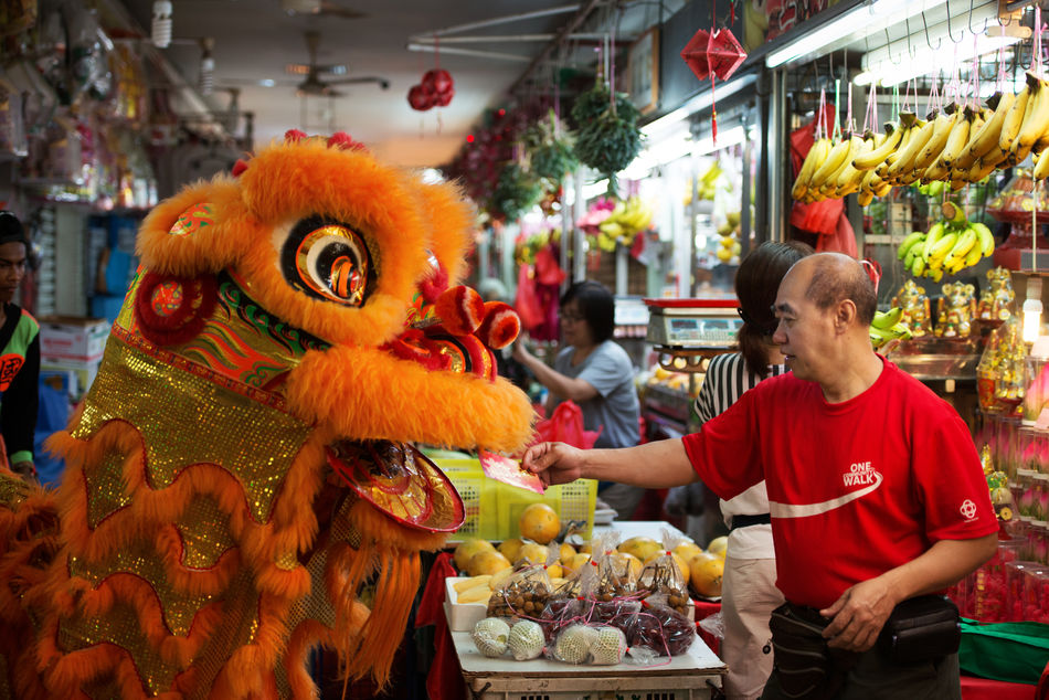 Man in dragon costume getting a donation from a shopkeeper