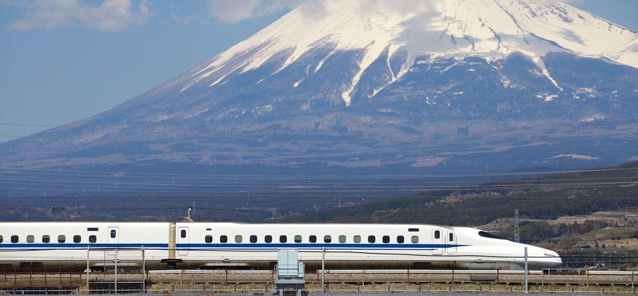 Tokaido Shinkansen bullet train passing Mt Fuji in Japan