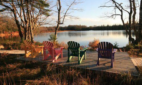 Four Adirondack chairs facing a Canadian lake