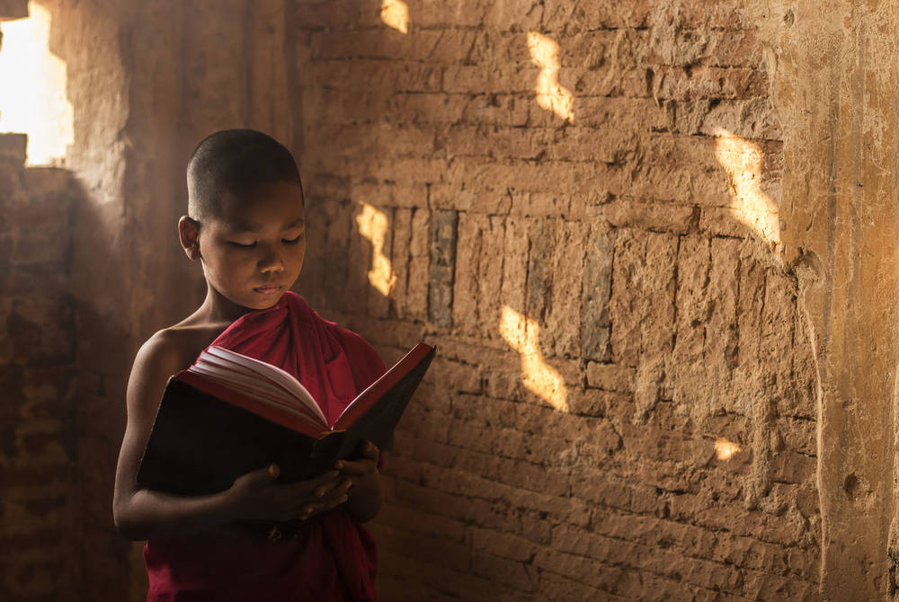 Young monk reading a book in Bagan
