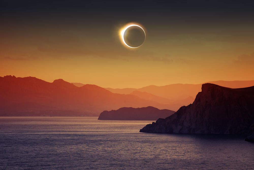 Total solar eclipse over lake and mountains