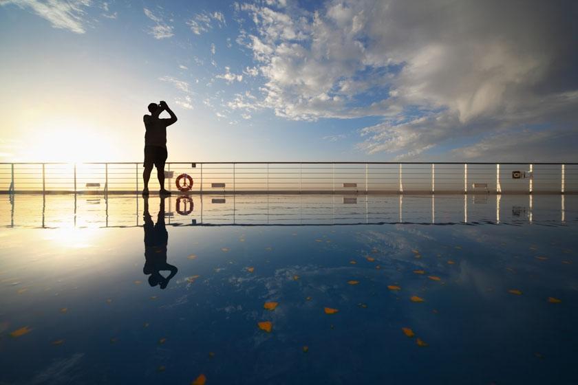 Cruise passenger capturing sunrise on deck