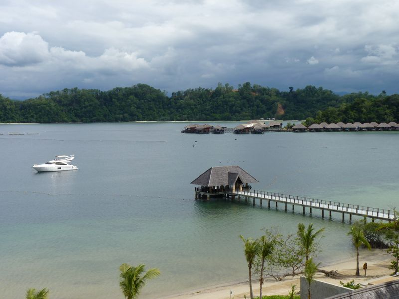Veranda view of jetty and Gaya island's luxury motor yacht